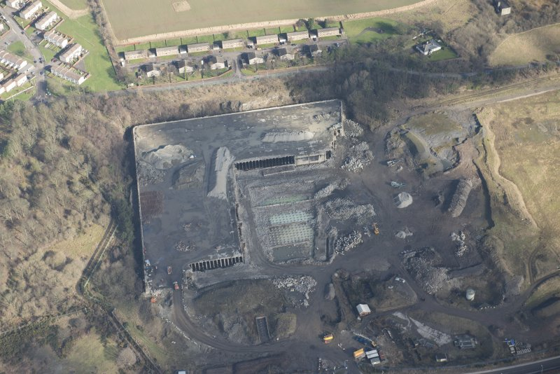 Oblique aerial view of partially demolished fuel oil store tank, looking NNE.
