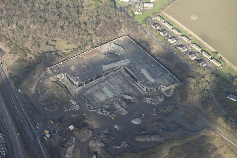 Oblique aerial view of partially demolished fuel oil store tank, looking NNW.
