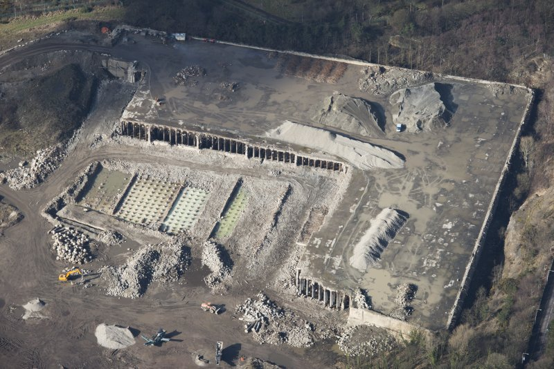 Oblique aerial view of partially demolished fuel oil store tank, looking W.