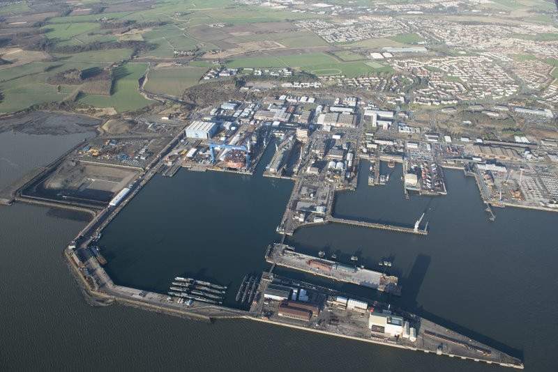 Oblique aerial view of HM Dockyard Rosyth centred on the Main Basin with the Goliath Crane beyond, looking NNE.