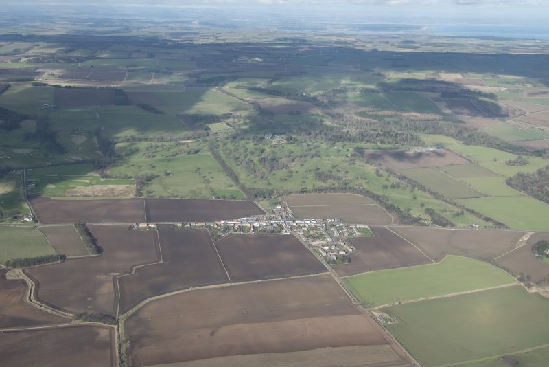 General oblique aerial view of Colinsburgh with Balcarres House policies in the background, looking N.