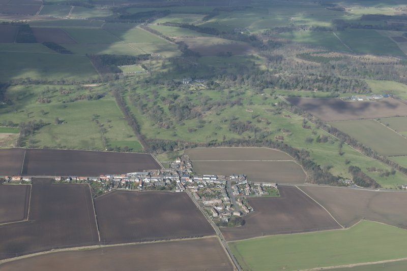 Oblique aerial view of Colinsburgh with Balcarres House policies in the background, looking N.