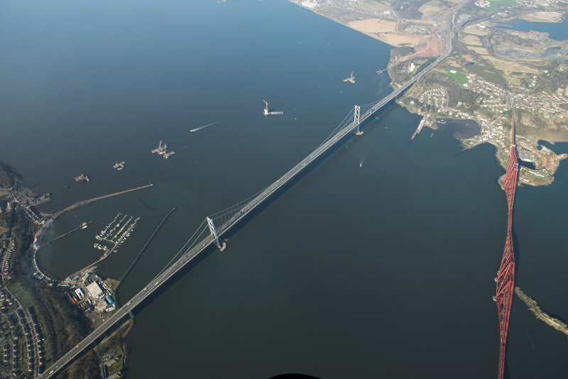 Oblique aerial view of the Forth Bridge, Forth Road Bridge and Queensferry Crossing construction, looking to the NNW.