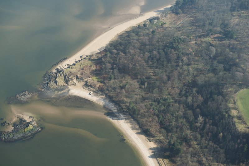 Oblique aerial view centred on the site of a wooden pier and location of possible gun emplacement, looking E.
