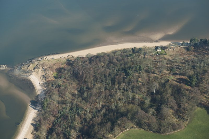 Oblique aerial view centred on the site of Hound Point Coast Battery, hidden by trees, and site of a wooden pier and location of possible gun emplacement, looking NE..