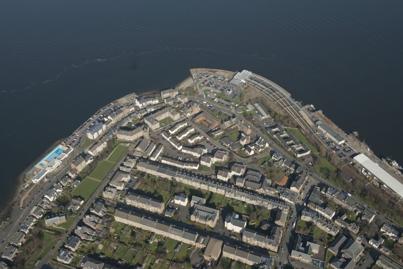 Oblique aerial view of Gourock station and pier and open air swimming baths, looking to the NE.