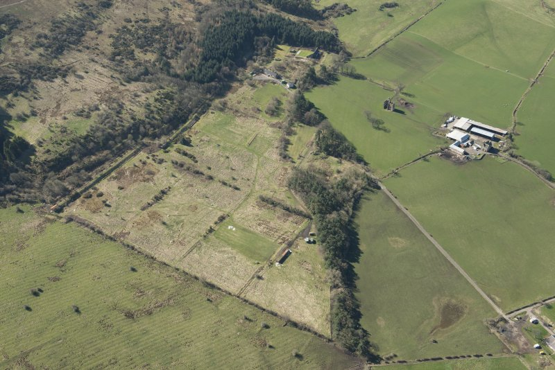 Oblique aerial view of part of the Dechmont Rifle Ranges and Gilbertfield Castle, looking SSW.