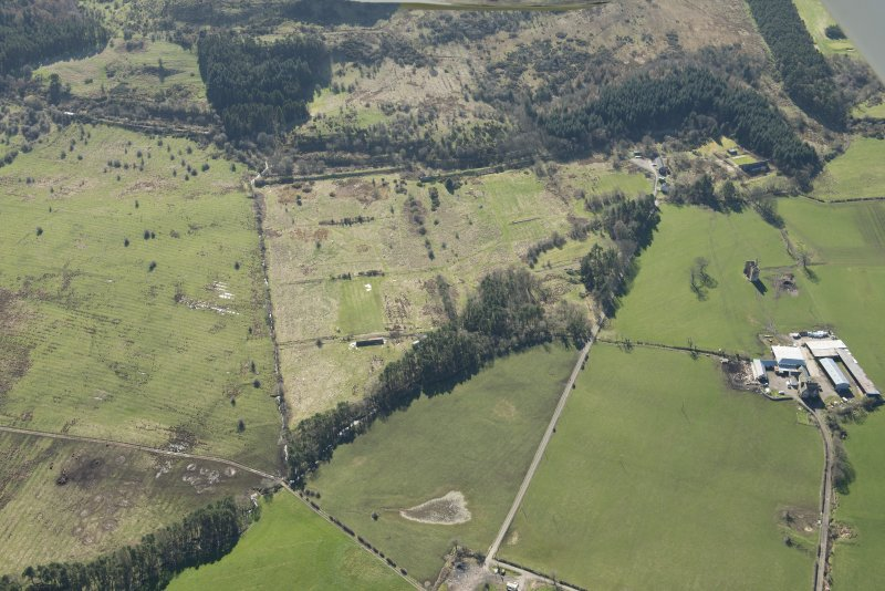 Oblique aerial view of part of the Dechmont Rifle Ranges and Gilbertfield Castle, looking SSE.
