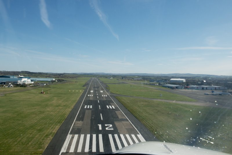 Forward oblique aerial view coming in to land on Runway 12, Prestwick Airport, looking SE.