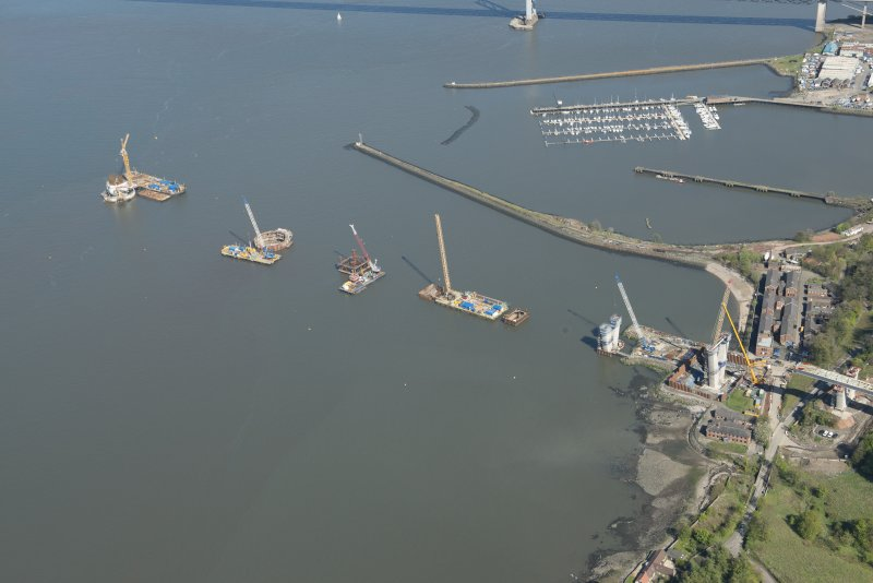 Oblique aerial view of the construction of the Queensferry Crossing on the south bank of the River Forth, looking E.