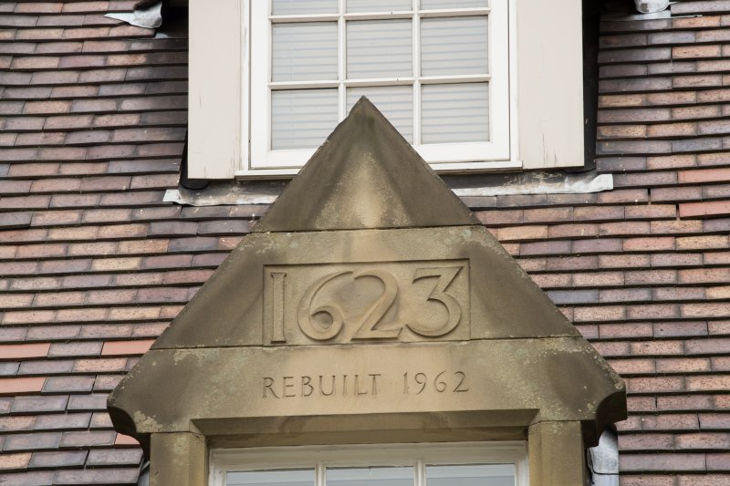 Detail of datestone in pediment '1623 REBUILT 1962' at 1-12 White Horse Close, 29 Canongate, Edinburgh.