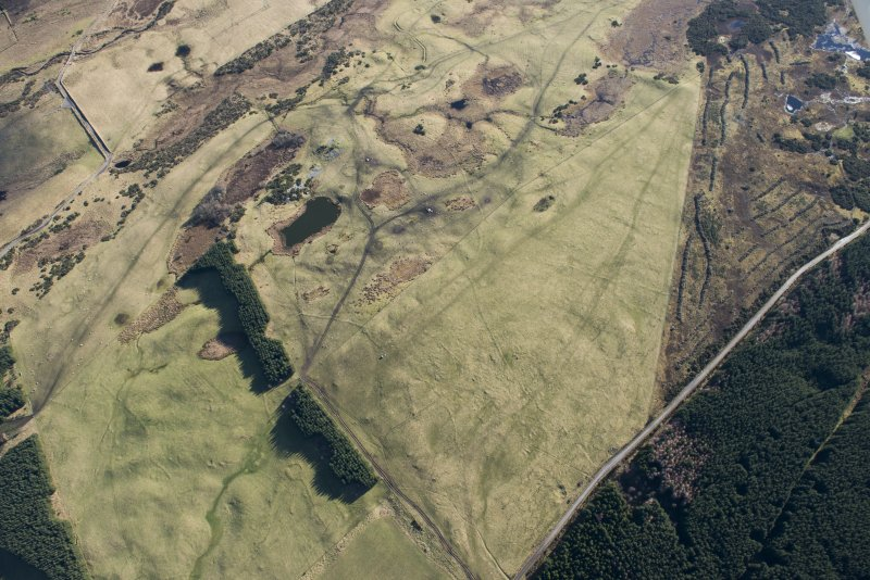 Oblique aerial view of hut circles, small cairns, field system and rig and furrow at Achvraid and Carn Glas cairns, looking SE.