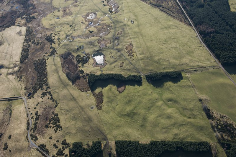 Oblique aerial view of Achvraid and Drumossie Moor field systems and Carn Glas cairns, looking SW.