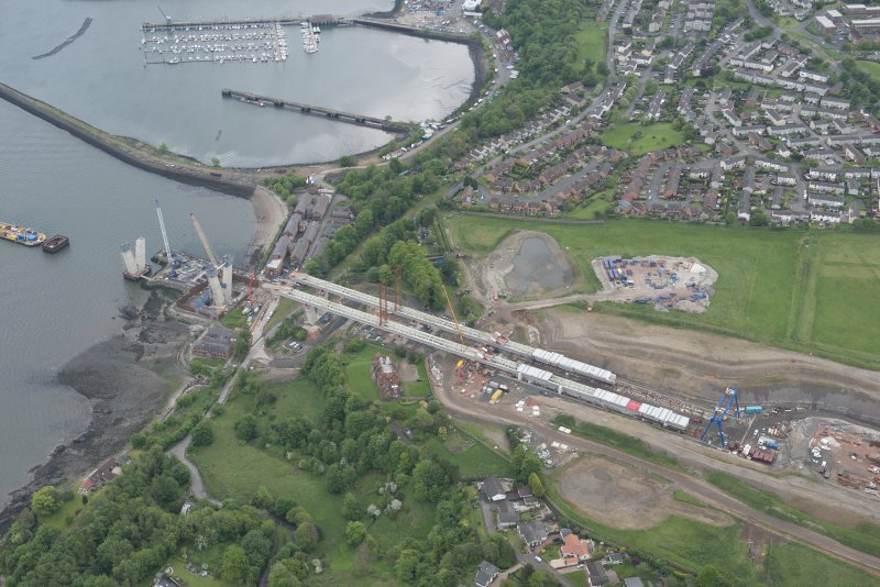 Oblique aerial view of the construction of the new Queensferry Crossing on the south bank of the Forth, looking E.