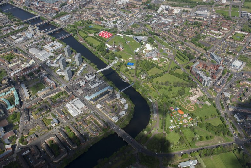 Oblique aerial view of Radio 1's Big Weekend at Glasgow Green, Nelson Monument and People's Palace, looking NNW.