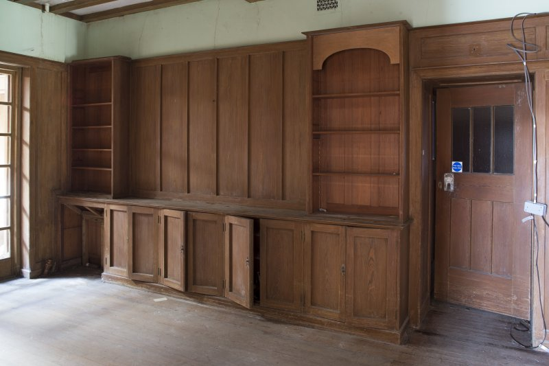 Detail of wooden shelving and cupboard unit in ground floor hall.