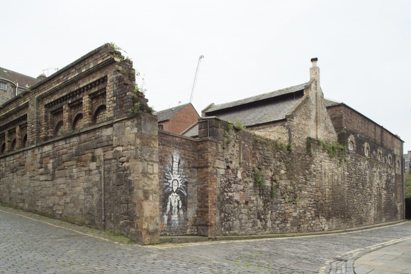 View of remnants of former boundary wall and buildings relating to former Gas Works, Old Tolbooth Wynd, Edinburgh, from NE.