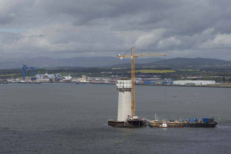 Forth crossing under construction. View of support pillar with crane and barge from road bridge to east