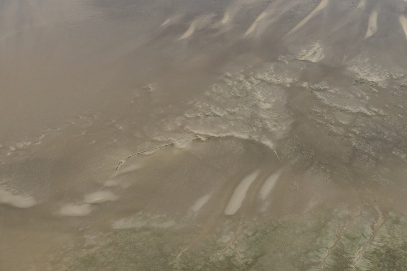 Oblique aerial view of the remains of the fish trap, looking ENE.