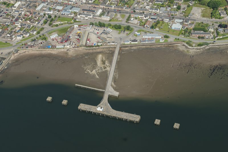 Oblique aerial view of Invergordon centred ont he pier, looking NW.