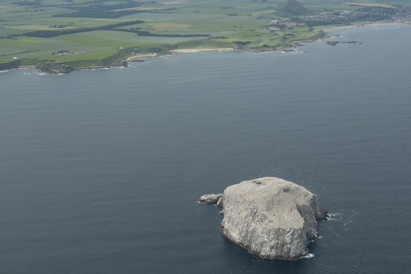 General oblique aerial view of the  Bass Rock with the East Lothian coastline beyond, looking SW.