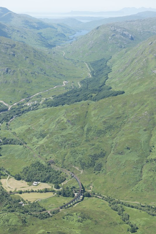 Oblique aerial view with the Glenfinnan railway viaduct in the foreground, looking SSW.