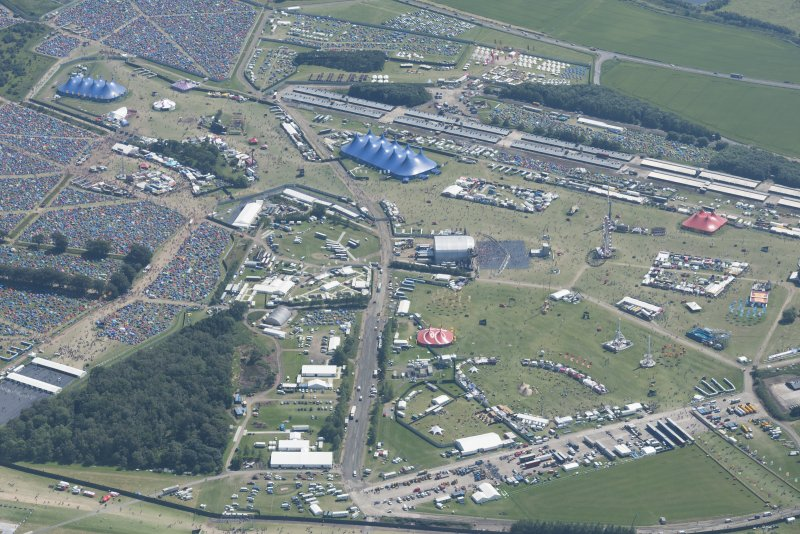 Oblique aerial view of T in the Park centred on the Main Stage with King Tuts Wah Wah Tent beyond, looking SSE.