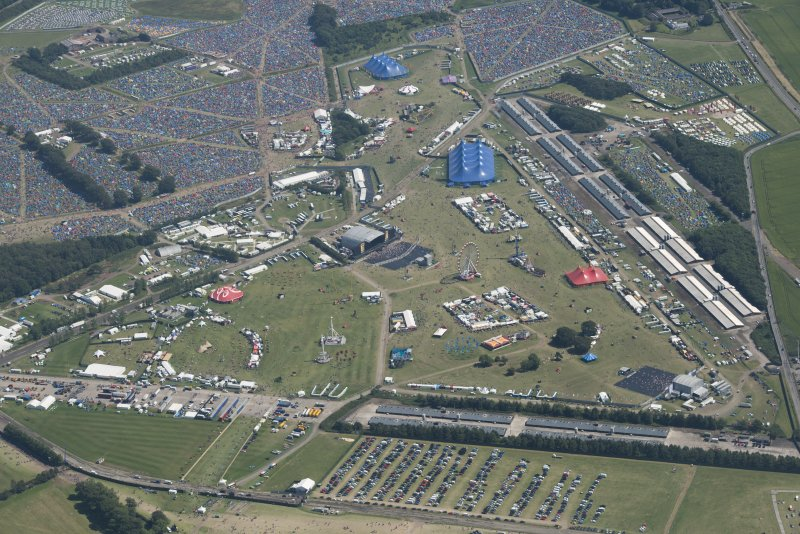 Oblique aerial view of T in the Park centred on the Main Stage with King Tuts Wah Wah Tent beyond, looking SE.