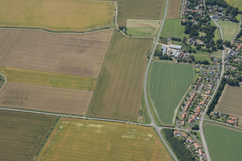 Oblique aerial view of the cropmarks of the field boundaries with Castle Mains Farm and Dirleton castle beyond, looking WSW.