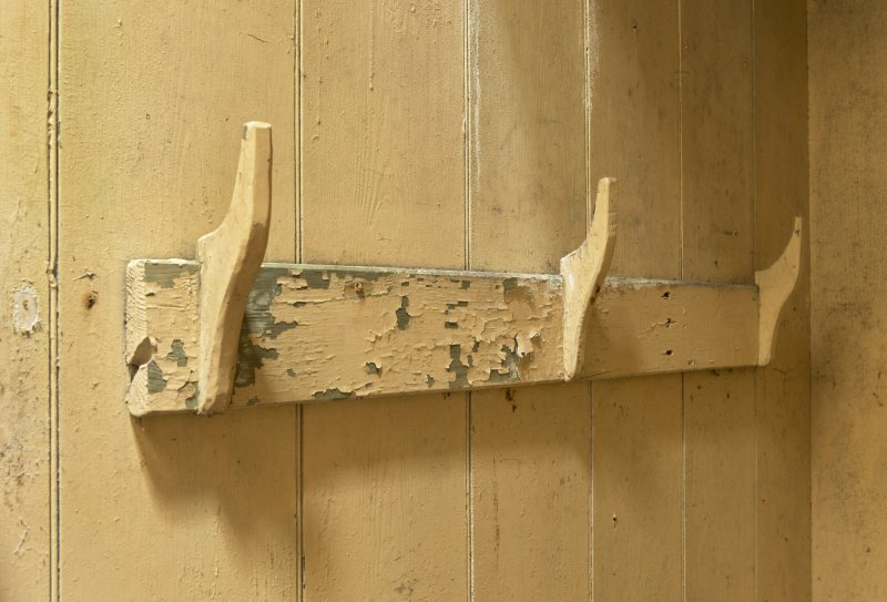 Entrance to north west range, ground floor, detail of wooden coat hooks