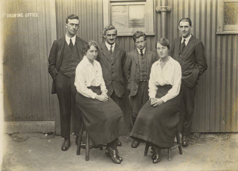 Uncaptioned photograph of a group of six people standing outside of a drawing office.