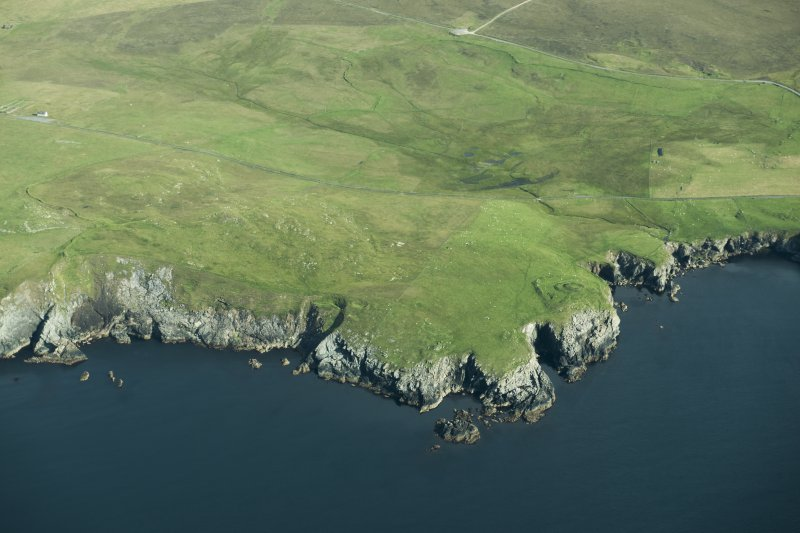 General oblique aerial view of Houbie Broch, Fetlar, looking N.