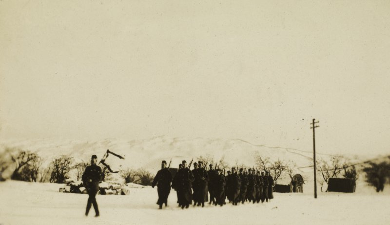 View of soldiers marching behind a piper at Stobs Camp.