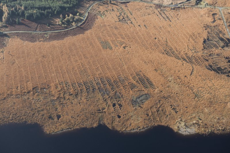 Oblique aerial view of the partially constructed Loch Doon airfield, showing the complex arrangement of field drains used to drain the peaty ground, looking WSW.