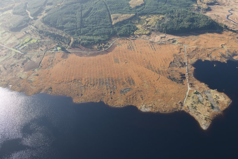 Oblique aerial view of the partially constructed Loch Doon airfield, showing the complex arrangement of field drains used to drain the peaty ground and site of the hangers, looking SW.