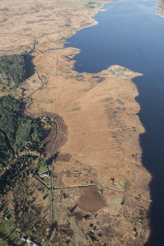 Oblique aerial view of the partially constructed Loch Doon airfield, showing the complex arrangement of field drains used to drain the peaty ground and site of an airplane hanger, looking NNW.
