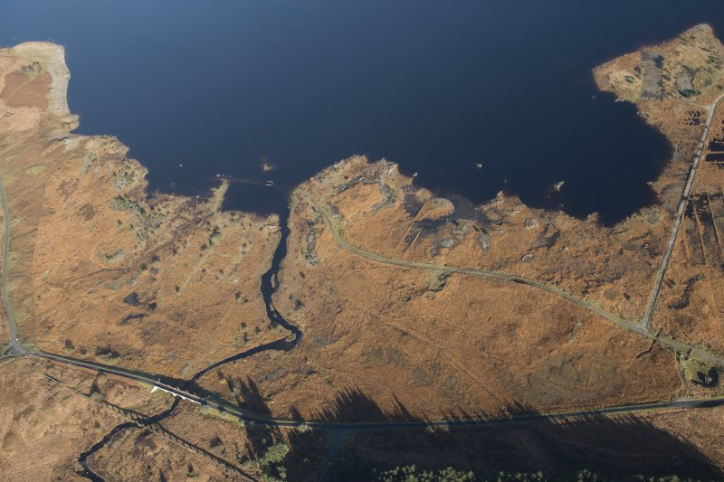 Oblique aerial view of a camp, a road bridge and the partially constructed Loch Doon airfield, looking NNE.