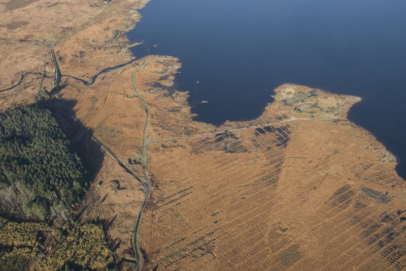 Oblique aerial view of the partially constructed Loch Doon airfield, showing the complex arrangement of field drains used to drain the peaty ground and concrete base of an airplane hanger, a road bridge and a camp,  looking NNW.