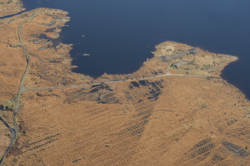 Oblique aerial view of the partially constructed Loch Doon airfield, showing the complex arrangement of field drains used to drain the peaty ground and concrete base of an airplane hanger, looking NNW.
