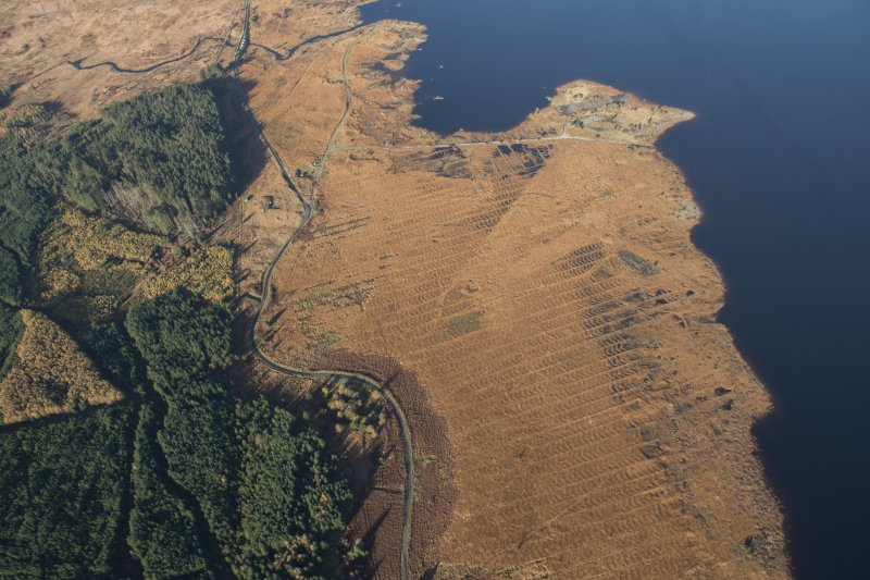 Oblique aerial view of the partially constructed Loch Doon airfield, showing the complex arrangement of field drains used to drain the peaty ground and concrete base of an airplane hanger, looking NE.