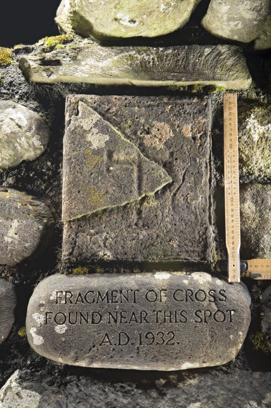 View of incised cross fragment built into north wall of burial ground (including scale)
