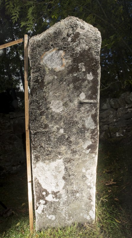 View of relief-carved cross slab. Peripheral lighting. (with scale)