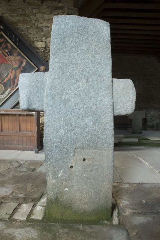 View of cruciform stone situated inside church.