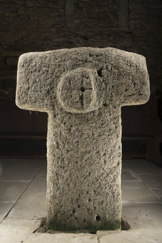 View of cruciform stone situated inside church. Peripheral lighting.