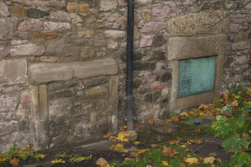 Detail of blocked openings (possibly reused stone) and commemorative plaque in south elevation of Harry Younger Hall, Lochend Close, Canongate, Edinburgh.