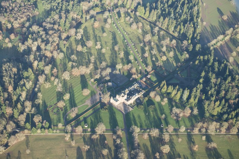 Oblique aerial view of Glamis Castle and policies, looking N.