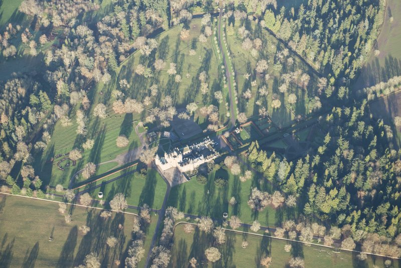 Oblique aerial view of Glamis Castle and policies, looking NNW.