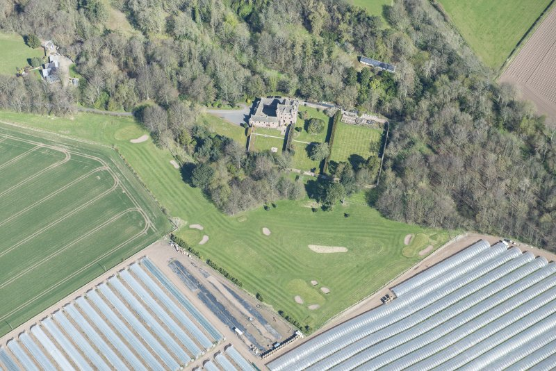 Oblique aerial view of Kellie Castle and the golf course, looking N.