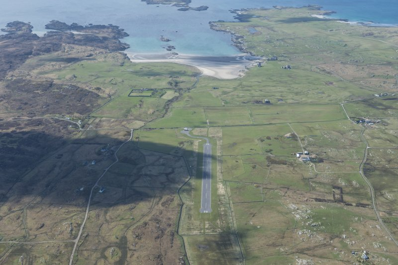 General oblique aerial view of Coll airfield with Breachacha castle and House beyond, looking SSW.