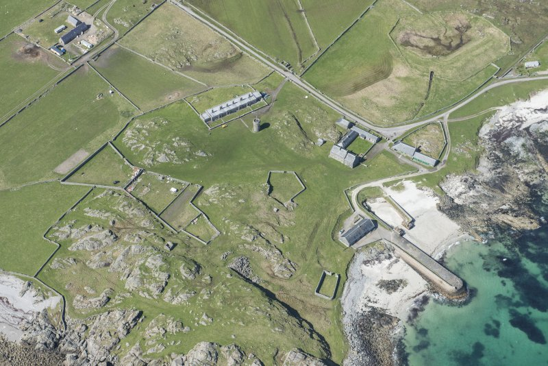 Oblique aerial view of Hynish Lighthouse shore establishment and harbour on Tiree, looking WNW.